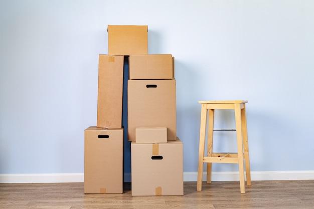 Cajas de cartón y taburetes apilados en una habitación.