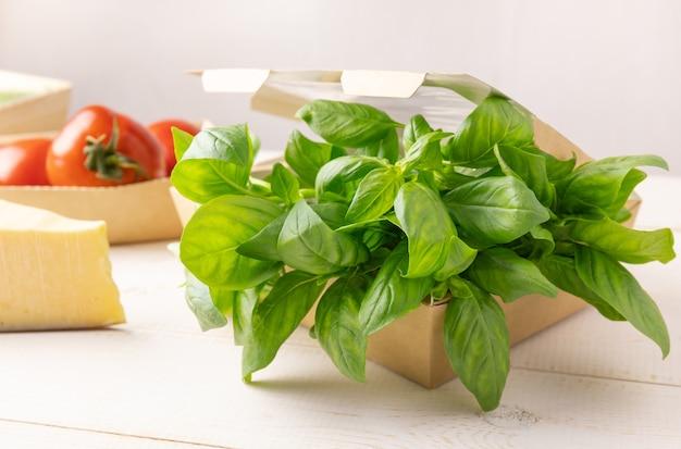 Cajas de cartón con tomates y albahaca
