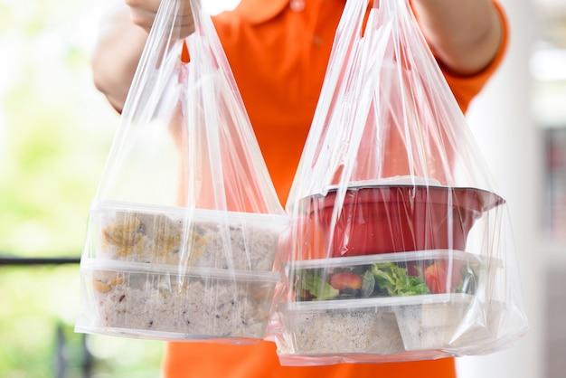 Cajas de comida asiática en bolsas de plástico entregadas al cliente en casa por el repartidor en uniforme naranja