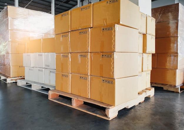 Cajas de envío de carga, pila de cajas de cartón sobre paletas en el almacén de almacenamiento.