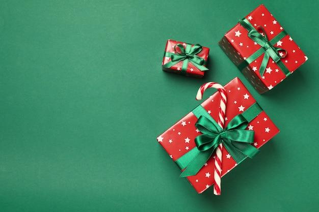 Cajas de navidad y bastón de caramelo en mesa verde
