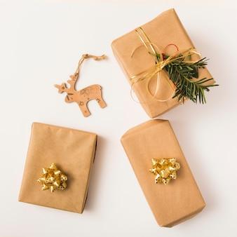 Cajas navideñas en papel artesanal con adorno festivo.