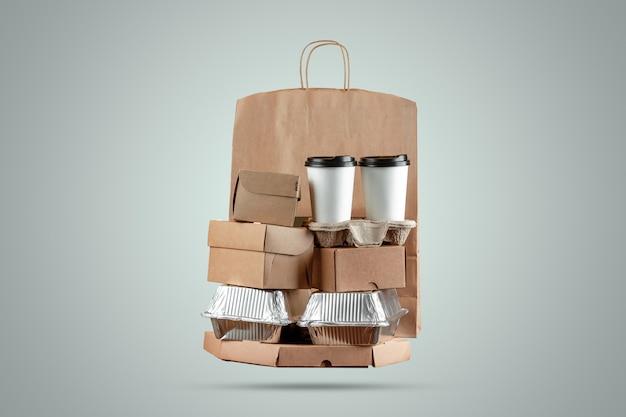 Cajas de pizza y bolsa de papel de entrega de alimentos con una taza de café desechable y una caja de wok sobre un fondo azul.