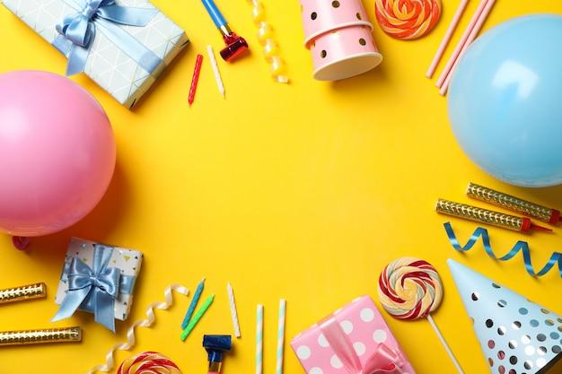 Cajas de regalo y accesorios de cumpleaños sobre fondo amarillo, espacio para texto
