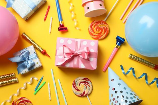 Cajas de regalo y accesorios de cumpleaños sobre fondo amarillo, vista superior