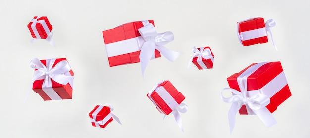 Cajas de regalo de banner rojo con lazo de cinta de raso volando sobre blanco.