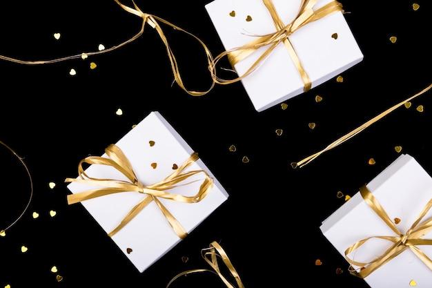Cajas de regalo blancas con cinta dorada sobre fondo de brillo