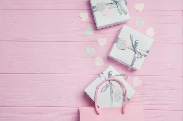 Cajas de regalo blancas con cinta de raso plateada en paquetes rosas y confeti en forma de corazón