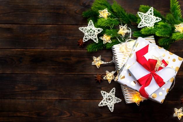 Cajas de regalo blancas y doradas con un lazo de cinta roja y ramas de árboles de navidad con estrellas trenzadas sobre un fondo de madera oscura con espacio de copia. vista superior, endecha plana. decoración de navidad, telón de fondo festivo.