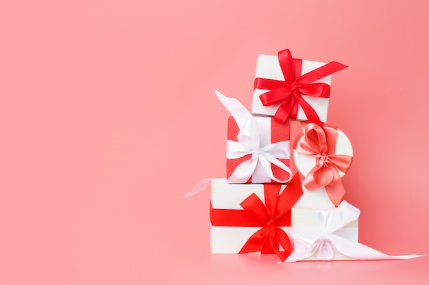 Cajas de regalo blanco con cintas de raso rojas sobre un fondo rosa. regalos festivos para el día de san valentín, día internacional de la mujer, boda o compromiso.