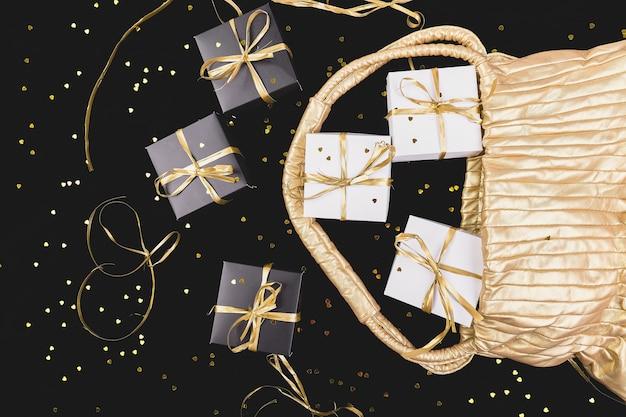 Cajas de regalo en blanco y negro con cinta dorada salen de la bolsa dorada en brillo. lay flat