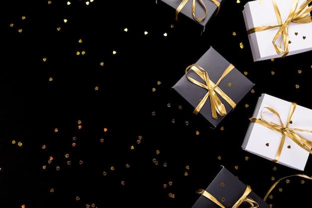 Cajas de regalo en blanco y negro con cinta dorada sobre fondo de brillo