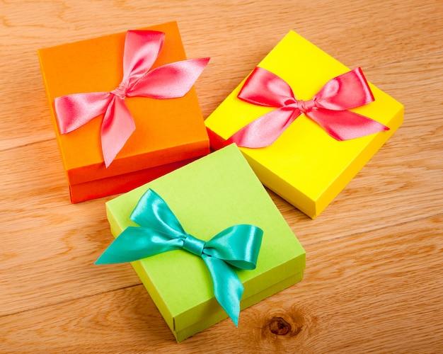 Cajas de regalo brillante colorido sobre fondo de madera