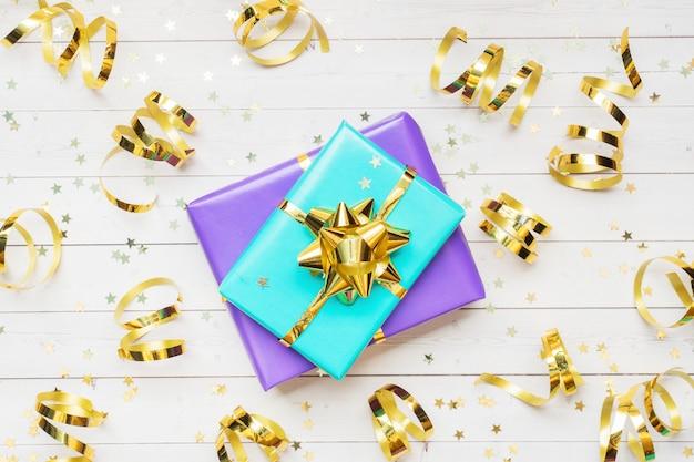 Cajas de regalo con cintas doradas y lazos, estrellas de confeti sobre una mesa blanca