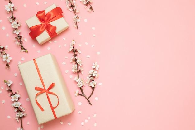 Cajas de regalo con cintas rojas, ramas de flores.
