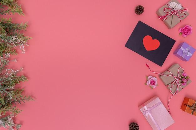 Cajas de regalo colocadas alrededor de una pizarra con un pequeño corazón rojo sobre una rosa