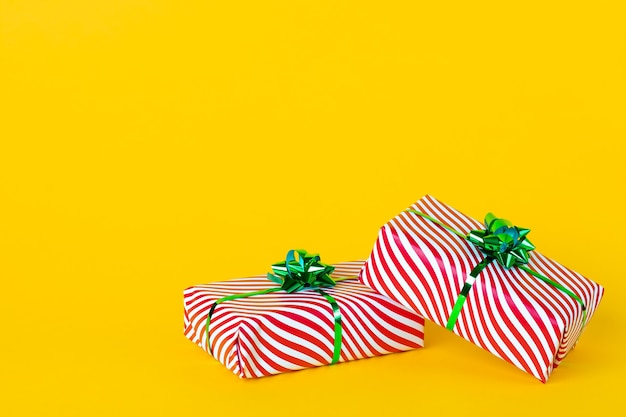 Cajas de regalo de colores con cinta sobre un fondo amarillo. copie el espacio, lugar vacío para el texto.