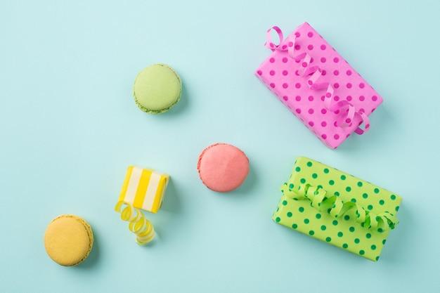 Cajas de regalo de colores y macarons en superficie azul claro