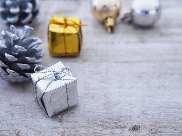 Cajas de regalo y cono de pino plateado en mesa de madera vintage blanco.