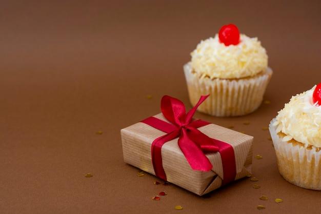 Cajas de regalo y cupcakes de vainilla con cereza en la parte superior. concepto de cumpleaños. postre dulce con espacio de copia de texto.
