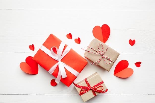 Cajas de regalo del día de san valentín y corazones de papel rojo sobre fondo blanco de madera