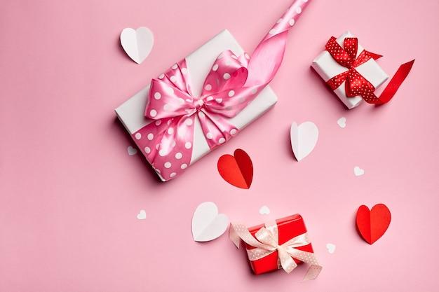 Cajas de regalo del día de san valentín con corazones de papel sobre fondo rosa
