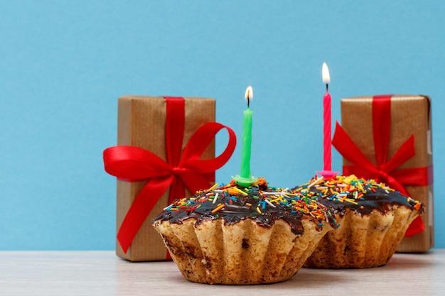 Cajas de regalo y dos deliciosos cupcakes de cumpleaños con glaseado de chocolate y caramelo, decorados con velas festivas encendidas sobre fondo azul. feliz cumpleaños concepto mínimo.