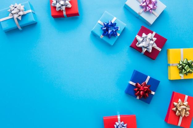Cajas de regalo envueltas coloridas con el arco en fondo azul
