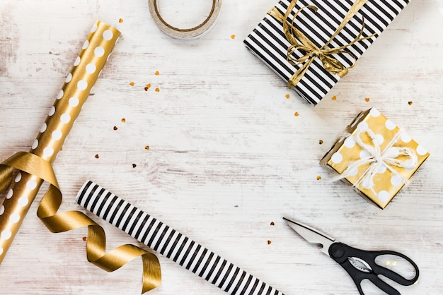 Cajas de regalo envueltas en papel rayado blanco y negro y punteado dorado y materiales de envoltura