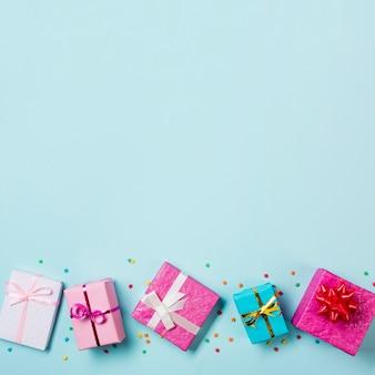 Cajas de regalo envueltas y rociadas en el fondo de fondo azul