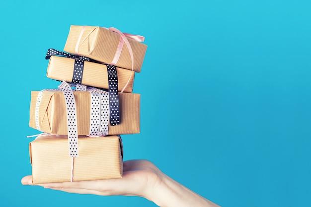 Cajas de regalo femeninas del control de la mano en un fondo azul, primer