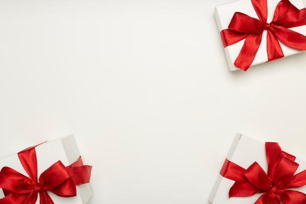 Cajas de regalo festivo con lazos rojos.