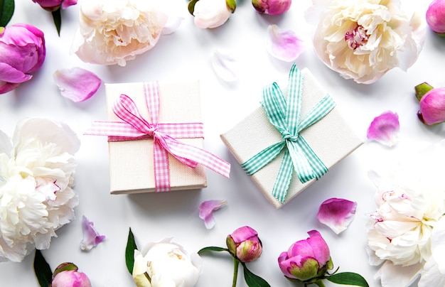 Cajas de regalo y flores aisladas en blanco