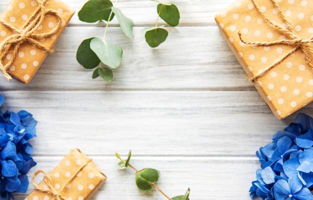 Cajas de regalo hechas a mano y flores azules sobre fondo de madera, vista superior