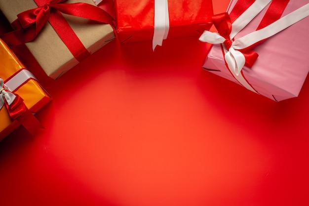 Cajas de regalo con lazo de cinta sobre fondo rojo.