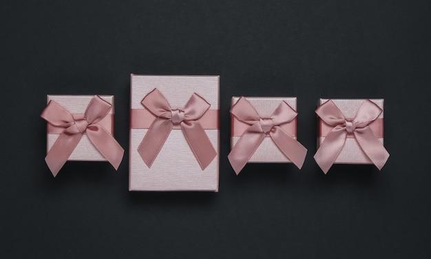 Cajas de regalo con lazo sobre fondo negro. composición para navidad, black friday, cumpleaños o boda.