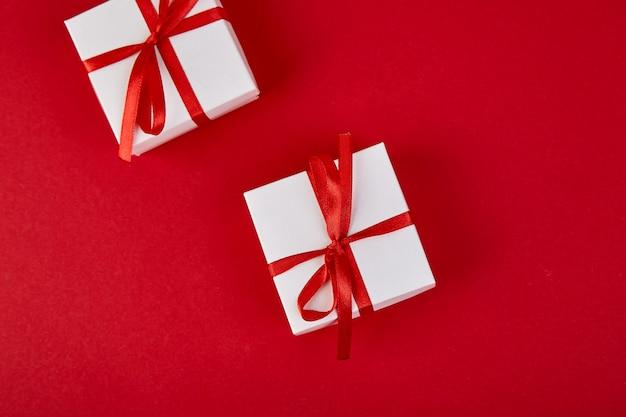 Cajas de regalo de lujo blanco con cinta roja sobre fondo rojo.