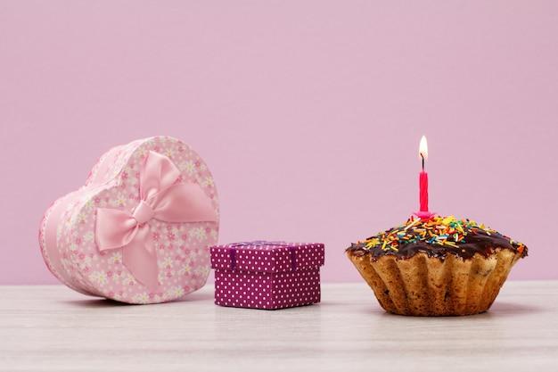 Cajas de regalo y muffin de cumpleaños sabroso con glaseado de chocolate y caramelo, decorado con velas festivas encendidas sobre fondo lila. feliz cumpleaños concepto mínimo.