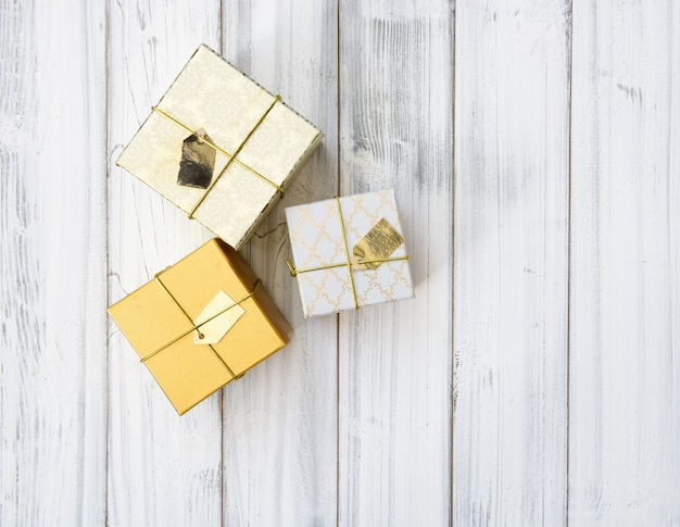 Cajas de regalo de navidad doradas sobre fondo blanco de madera, plano laical