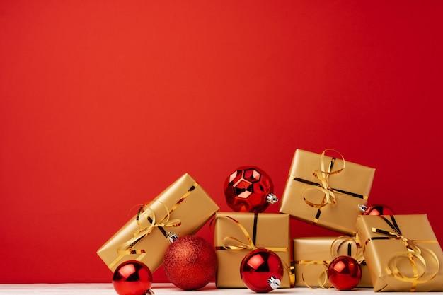 Cajas de regalo de navidad envuelto contra la vista frontal de fondo rojo
