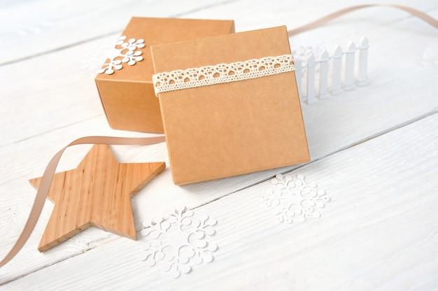 Cajas de regalo de navidad con una estrella de madera y corazón, copos de nieve