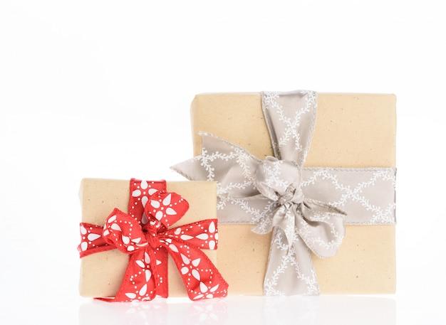 Cajas de regalo de navidad marrón envuelto con cinta roja aislado sobre fondo blanco.