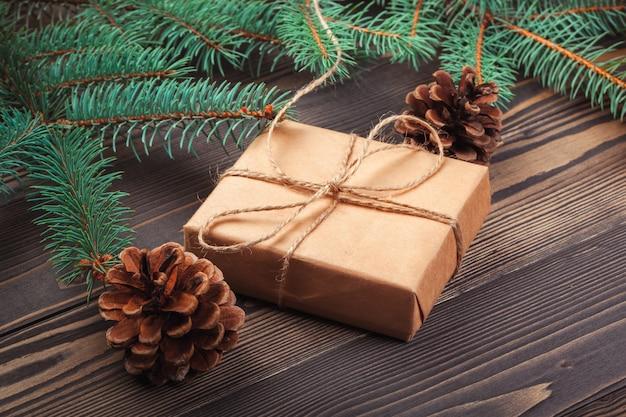 Cajas de regalo de navidad y rama de abeto en mesa de madera.