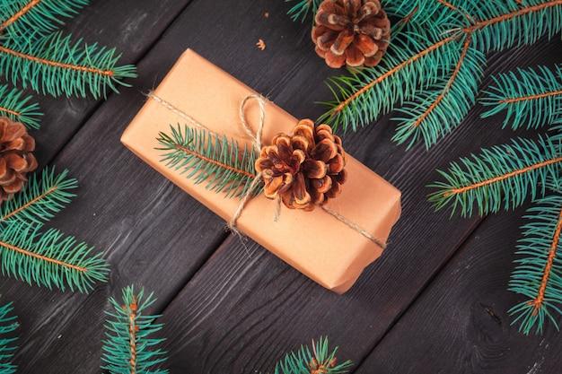 Cajas de regalo de la navidad y rama de árbol de abeto en la tabla de madera.