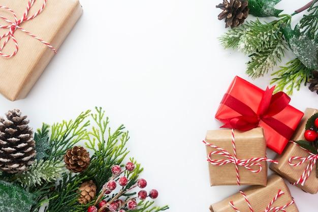 Cajas de regalo de navidad, ramas de abeto de estilo, conos de pino, fondo blanco.