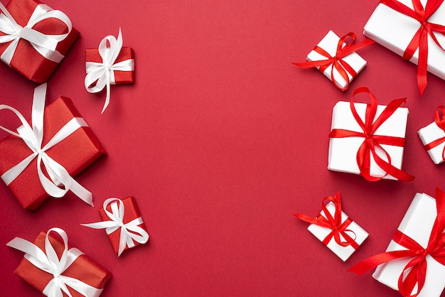 Cajas de regalo de navidad rojo y blanco de año nuevo sobre fondo rojo endecha plana