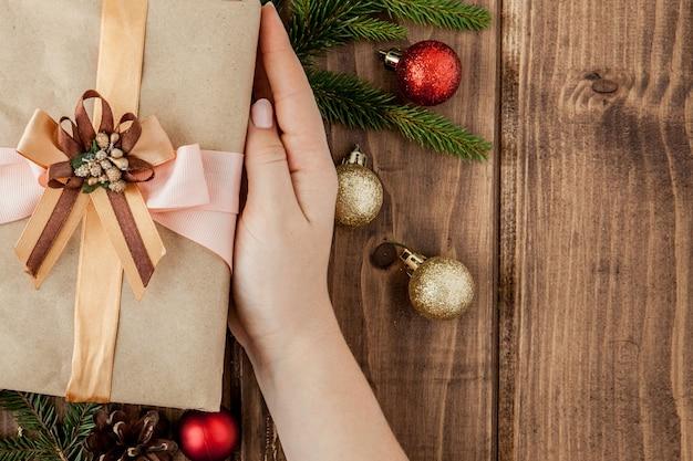 Cajas de regalo de navidad, rollos de papel y decoraciones en rojo. preparación para vacaciones. vista superior con espacio de copia. manos de mujer con caja de regalo
