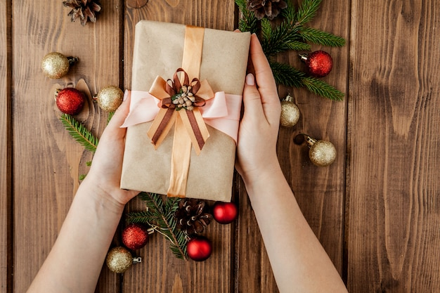 Cajas de regalo de navidad, rollos de papel y decoraciones en rojo. preparación para vacaciones. vista superior. manos de mujer con caja de regalo