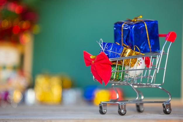 Cajas de regalo de navidad en varios colores colocadas en un carrito de compras