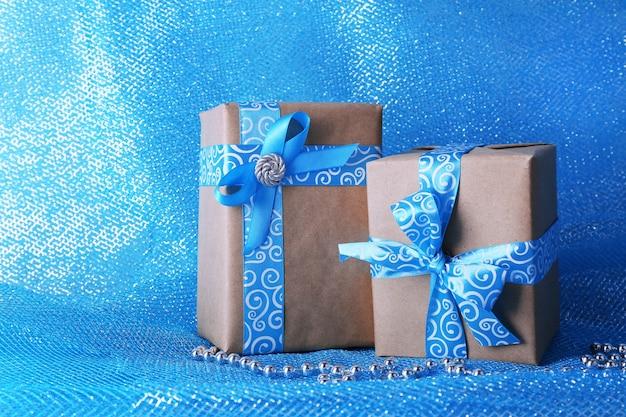 Cajas de regalo navideñas decoradas con cinta azul sobre fondo de tela azul